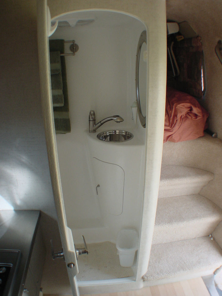 The-bathroom-also-features-a-stainless-steel-sink-and-a-full-fiberglass-shower-area