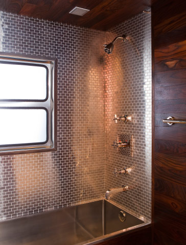 The bathroom features a satinless steel deep soak bathtub