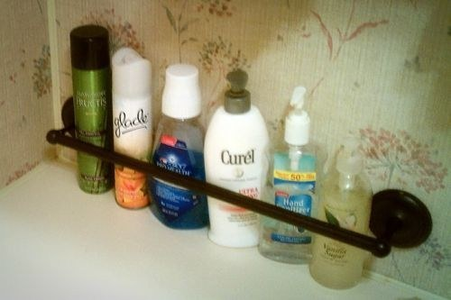 a towel rod is an easy hack to keep your bath products in place